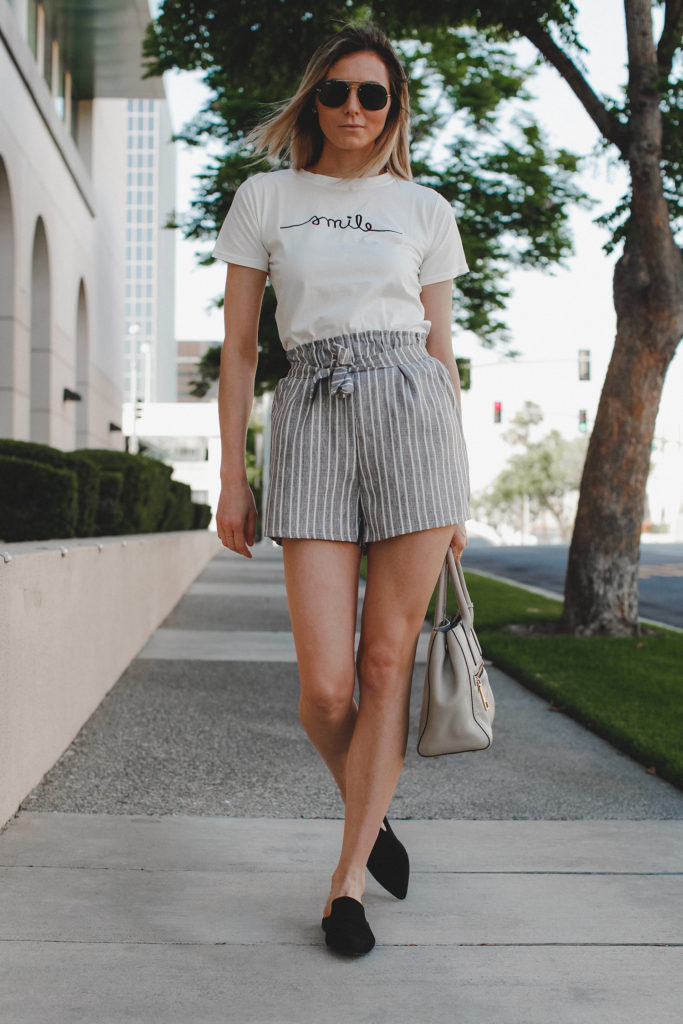 Paper bag shorts trend featured by top US fashion blog, Tea Cups & Tulips: image of a woman wearing Light grey paper bag shorts and a smile tee