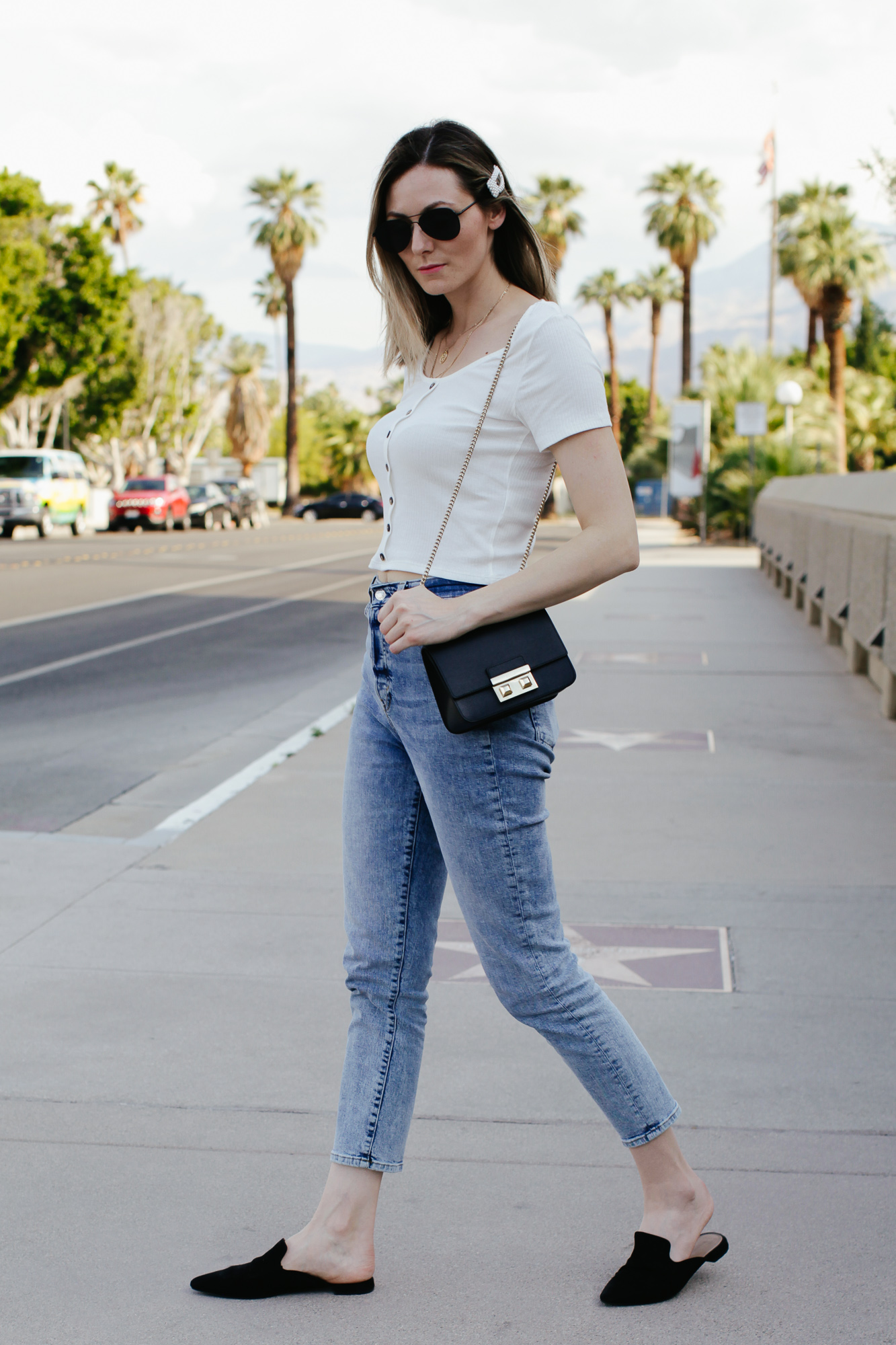 How to wear mom jeans, styling tips featured by top US fashion blog, Tea Cups & Tulips: image of a woman wearing H&M high waisted mom jeans, H&M ribbed top, A New Day pointy mules, Fulra bag, Amazon SOJOS aviator sunglasses and Amazon pearl hair clip.