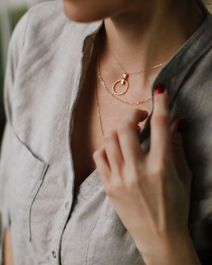 Dainty gold necklaces. How to layer necklaces. | Dainty Gold Necklaces and How to Layer Them by popular fashion blog, Tea Cups and Tulips: image of a woman wearing layered dainty gold necklaces.