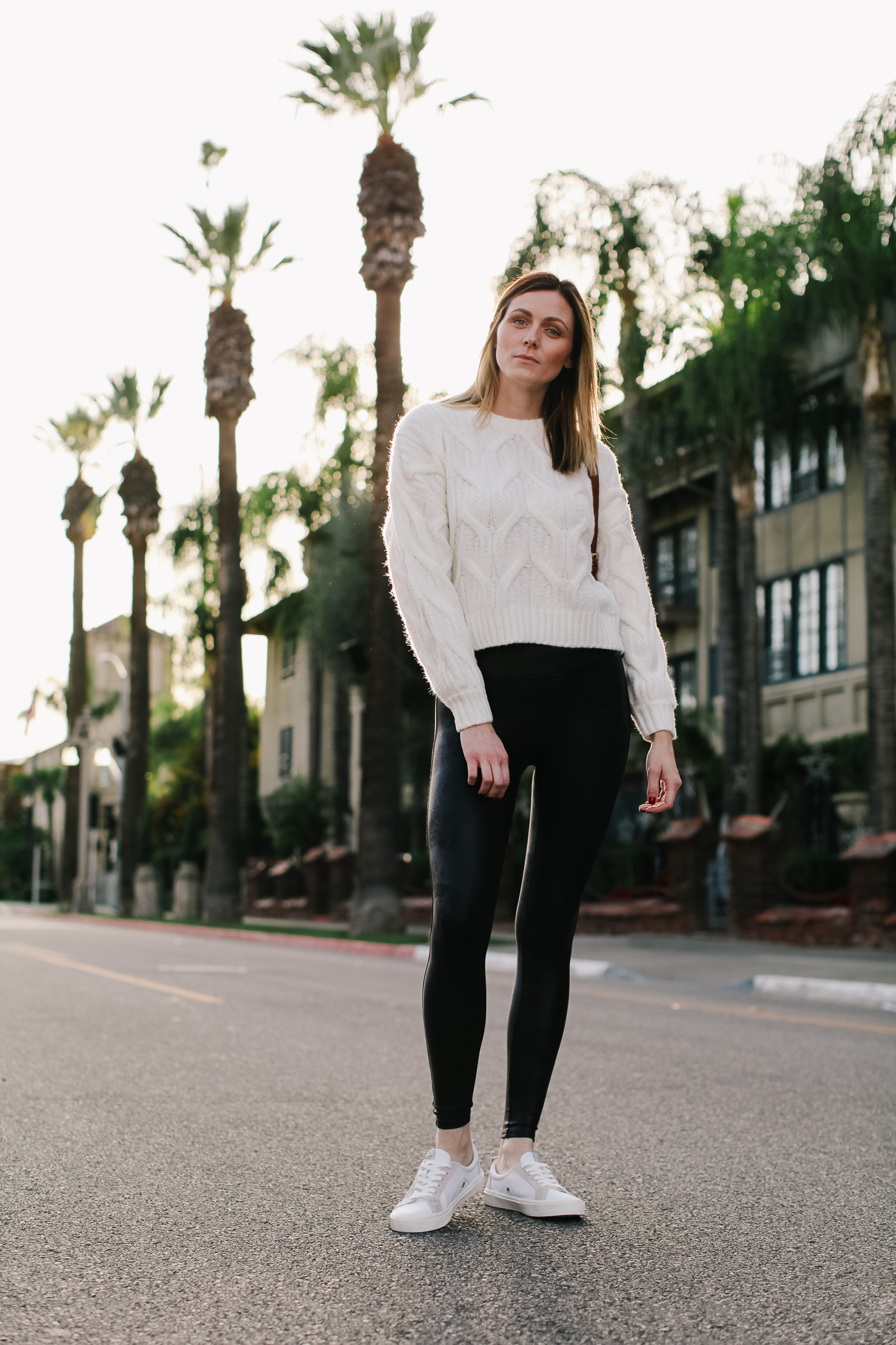 Spanx Faux Leather Leggings Review by popular LA fashion blog, Tea Cups and Tulips: image of a woman wearing a white sweater, white sneakers, and Spanx faux leather leggings.