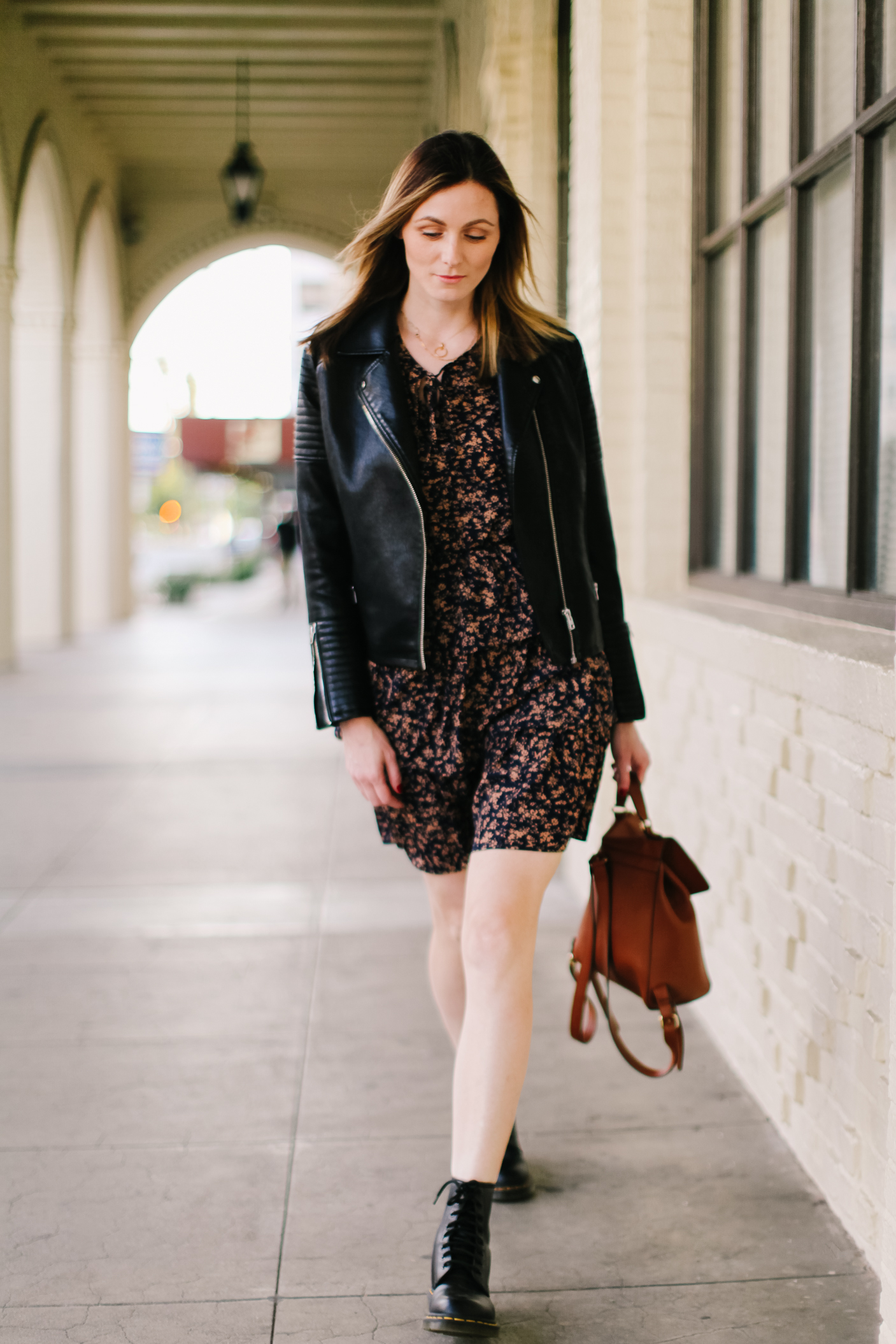 Black Floral Ruffle Dress | Floral Ruffle Dress by popular LA fashion blog, Tea Cups and Tulips: image of a woman wearing a SheIn Ditsy Floral Layered Ruffle Hem A-line Dress, leather jacket, and Dr Martens Vegan 101 6 eye boots in black.