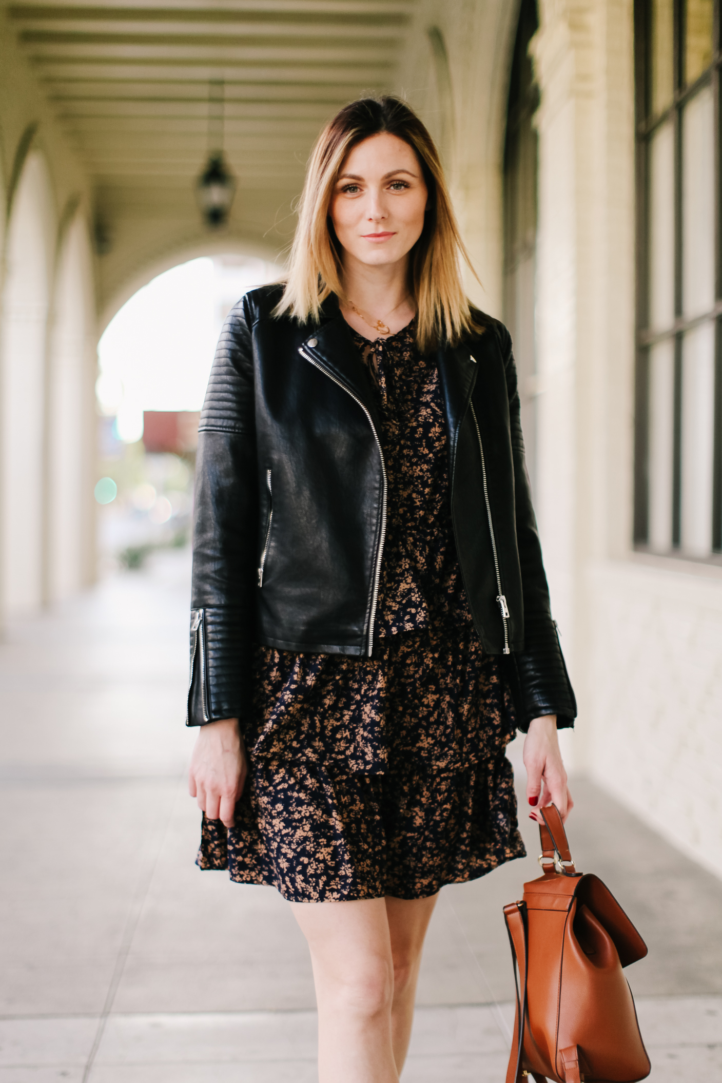 Floral Ruffle dress and faux leather jacket | Floral Ruffle Dress by popular LA fashion blog, Tea Cups and Tulips: image of a woman wearing a SheIn Ditsy Floral Layered Ruffle Hem A-line Dress, leather jacket, and Dr Martens Vegan 101 6 eye boots in black.